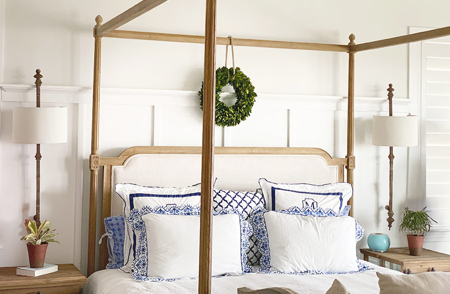 Vintage metal faux patina architectural sconces on either side of bed in a bedroom
